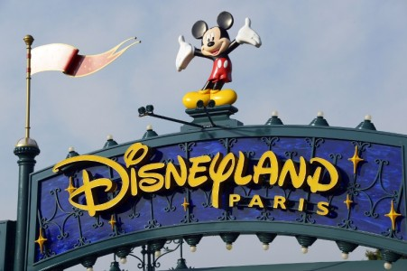 """(FILES) This file photo taken on August 13, 2015 shows a sign above the entrance at Disneyland Paris in Marne-la-Vallee. A man carrying two handguns, ammunition and a Koran was arrested on January 28, 2016 at a hotel in Disneyland Paris, police sources said. The man was """"detected upon his arrival at the Disneyland hotel where he had a reservation. Hotel security found two handguns, a Koran and ammunition on him"""", said the source.  / AFP / BERTRAND GUAY"""
