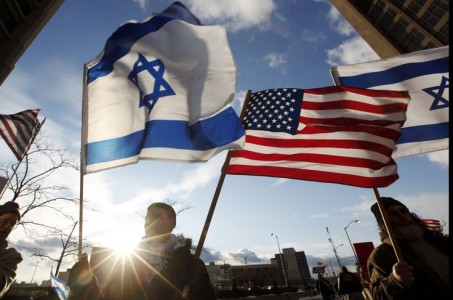 A man carries a Israeli and U.S. flag during a counter protest to a pro-Palestinian protest outside the Patrick V. McNamara Federal Building in Detroit, Thursday, Jan. 8, 2009. A few dozen supporters of Israel carried Israeli and U.S. flags and signs condemning Hamas, the Islamic militants who rule Gaza. (AP Photo/Paul Sancya)