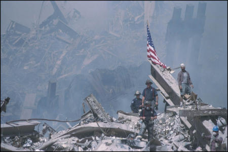 Workers work to save any survivors from the rubble of the WTC. rubble debris rescue firefighters recovery ground zero search bucket brigade flag
