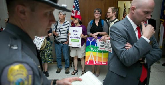 Surrounded by several layers of security, activists against HB2 start a peaceful protest outside the office of House Speaker Tim Moore at the State Legislative Building in Raleigh, N.C., on Monday, April 25, 2016. (Robert Willett/Raleigh News & Observer/TNS)