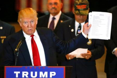 """U.S. Republican presidential candidate Donald Trump holds paperwork which states """"Donald J. Trump, Veteran Fundraiser"""" during a news conference at Trump Tower in Manhattan, New York, U.S., May 31, 2016. REUTERS/Carlo Allegri"""