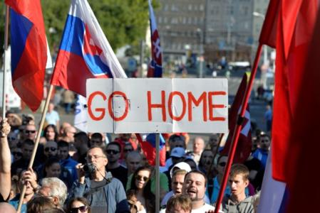 """TOPSHOTS Participants hold flags and a banner during an anti-immigration rally organised by an initiative called """"Stop Islamisation of Europe"""" and backed by the far-right """"People's Party-Our Slovakia"""" on September 12, 2015 in Bratislava, Slovakia. AFP PHOTO / Samuel Kubani"""