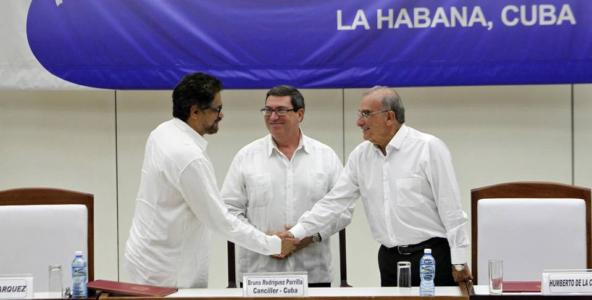 FARC delegation leader Luciano Marín, alias 'Iván Márquez', left, shakes hands with the Colombian government's chief negotiator Humberto de la Calle, right, before Cuban Foreign Minister Bruno Rodríguez in Havana, Cuba, after the final peace agreement was signed on Wednesday.