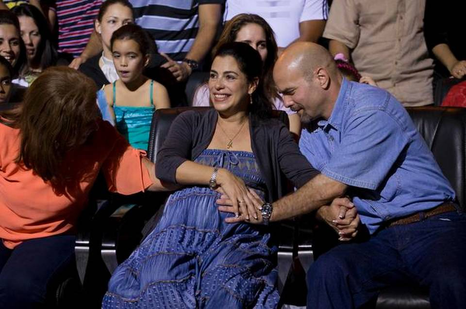 "Gerardo Hernandez, right, a member of ""The Cuban Five,"" touches the belly of his pregnant wife, Adriana Perez, during a concert in Havana on Saturday, Dec. 20, 2014. The pregnancy came through artificial insemination while Hernandez was being held in the U.S."