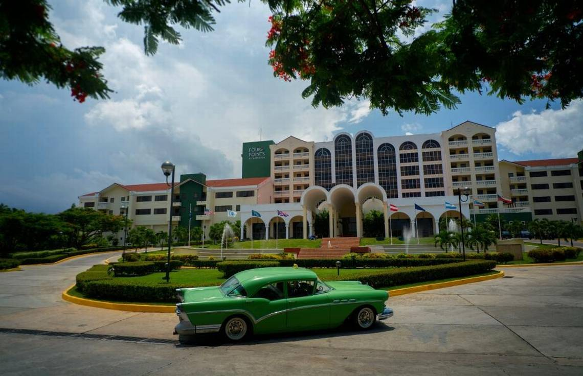 In this June 28, 2016 file photo, a vintage car passes in front of the Four Points by Sheraton hotel in Havana, Cuba, managed vy the U.S.-based Starwood hotel chain and owned by Gaviota, part of the military conglomerate known as GAESA.