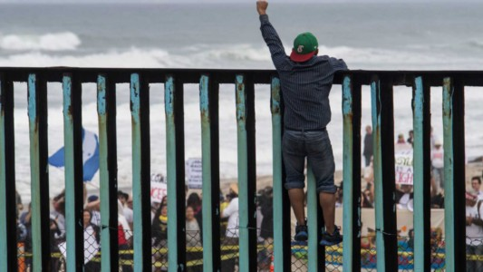 Refugees In 'Caravan' Climb U.S.-Mexico Border Fence, Chant 'Yes We Can!'